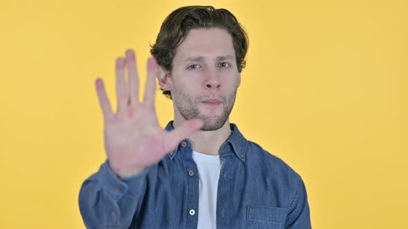 Thumbnail for Stop Sign By Young Man, Hand Gesture on Yellow Background