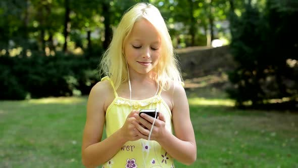 Thumbnail for Little Cute Girl Listen Music in the Park on the Smartphone Through the Headphone