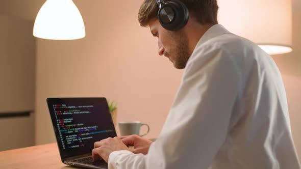 Male Programmer is Working on Creating Software Typing Program Code on a Laptop Keyboard Programmer