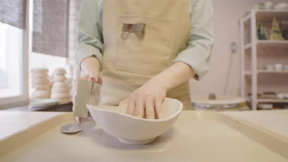 Female Potter Sanding Clay Bowl with Abrasive Brick