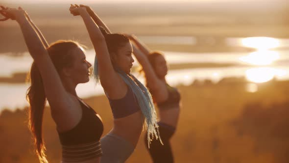 Three Young Women Doing Aerobic Exercises on Sunset