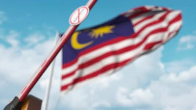 Barrier with No Immigration Sign Closed with Flag of Malaysia