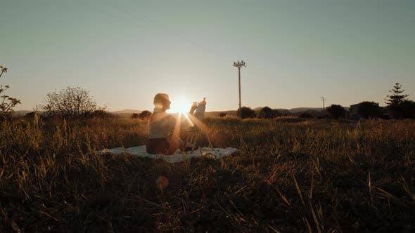 Mädchen malt bei Sonnenuntergang auf einem Feld auf dem Boden sitzend