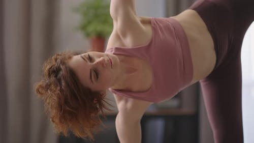 Adult Pretty Woman is Practicing Hatha Yoga at Home Performing Asana for Balance and Endurance