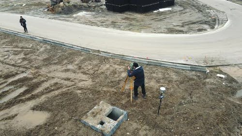 Aerial View Surveyors Measuring the Ground Level to Create a Landscape of Newly Created Construction