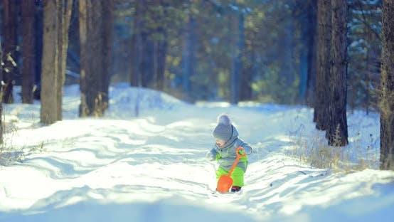 Junge isst Schnee mit Fäustlingen