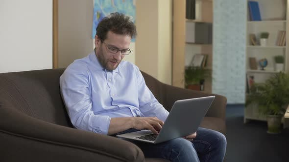 Thumbnail for Man With Eyeglasses Sitting on Sofa and Shopping Online on Laptop, Technologies