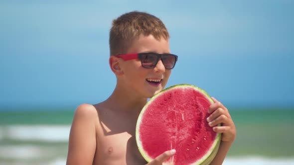 Thumbnail for The Boy in Glasses Holds a Bright Watermelon on the Background of the Sea
