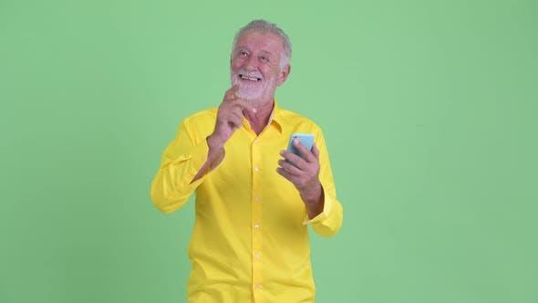 Cover Image for Happy Senior Bearded Businessman Thinking While Using Phone