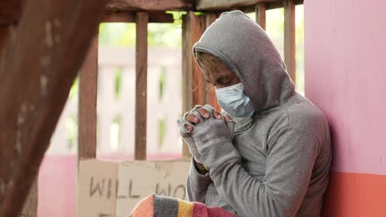 Homeless man in face mask is praying