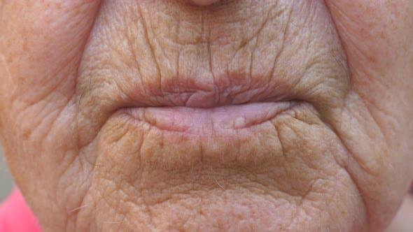 Thumbnail for Close Up Lips of Mature Grandmother. Mouth of Elder Grandma Sends Air Kiss Into Camera. Senior Woman
