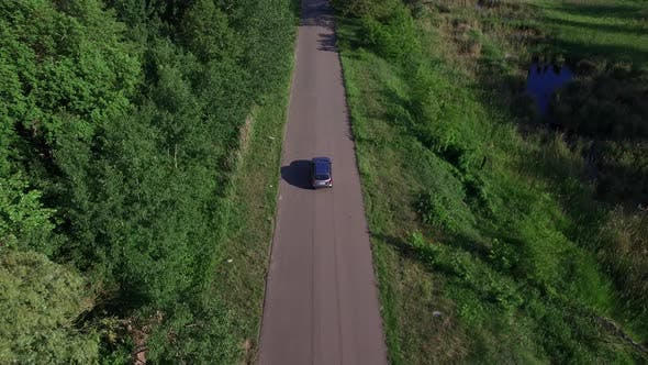 Thumbnail for Drone View Car Driving on Countryside Road Through Green Forest