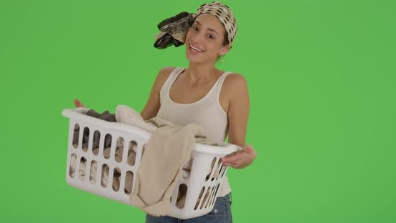 Thumbnail for A Hispanic woman does her laundry as she poses for a portrait on green screen