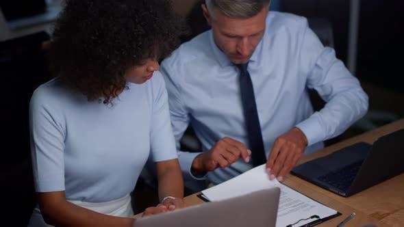 Thumbnail for Geschäftsfrau und Geschäftsmann arbeiten mit Finanzdokumenten im Büro