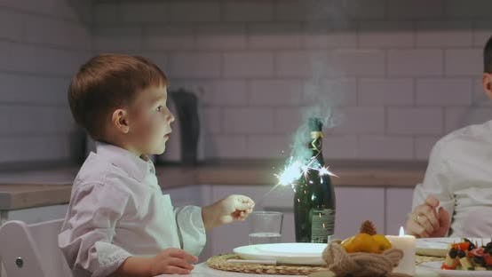 Thumbnail for A Boy Holds and Looks Joyfully at a Sparkler Sitting at Dinner on Christmas Eve