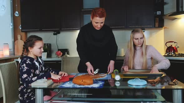 Women Baking Gingerbread Cookies in the Kitchen at Home