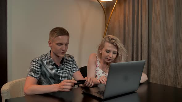 Attractive Guy and Girl Sit on the Coucand Shop Online with Credit Card on the Laptop Notebook.