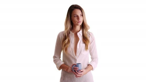 Thumbnail for Pensive woman holding coffee mug on white background with copyspace