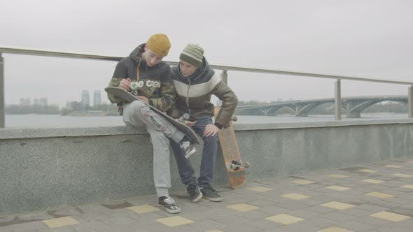Thumbnail for Teen Boys Checking Wheel Mounting on Skate Outdoor