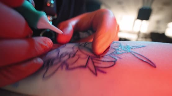 Tattoo Artist Makes a Tattoo on a Arm, Works in Studio. Close-up View Slow Motion
