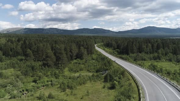 Thumbnail for Aerial of the empty road going through forest