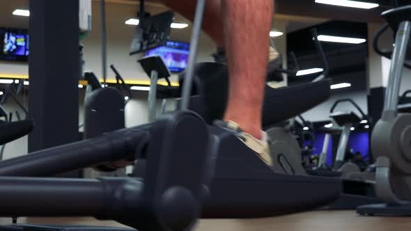 Thumbnail for A Fit Man Trains on an Elliptical Trainer in a Gym - Closeup on the Feet