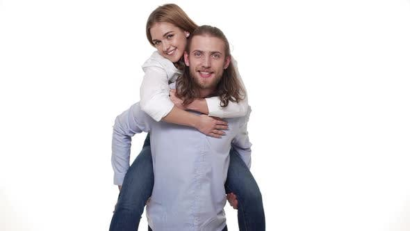 Thumbnail for Couple Having Fun with Piggyback Ride Over White Background