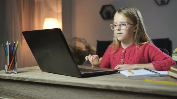 Thumbnail for Cheerful Child Doing Homework Online with Laptop