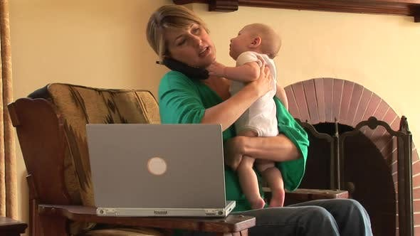 Thumbnail for New mother with laptop and cell phone holding new baby