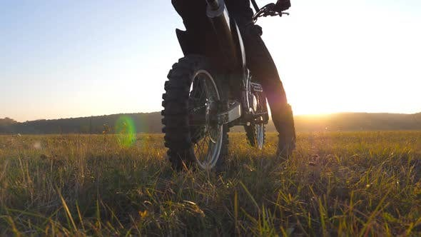 Thumbnail for Unrecognizable Motorcycle Rider Sits on His Motorcycle Amid Large Field on Beautiful Sunset