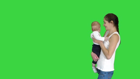 Thumbnail for Happy Mother Kissing Adorable Baby auf grünem Bildschirm, Chroma Key.