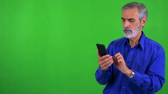 Thumbnail for Old Senior Man Works (Typing) on Smartphone - Green Screen - Studio