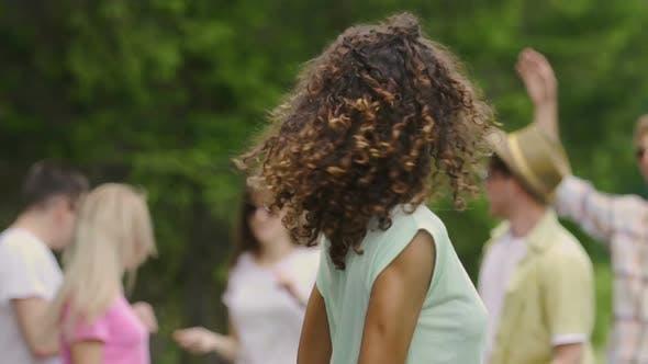 Thumbnail for junge hübsche frau mit lockigem haar tanzen bei picknick mit freunden sommerzeit