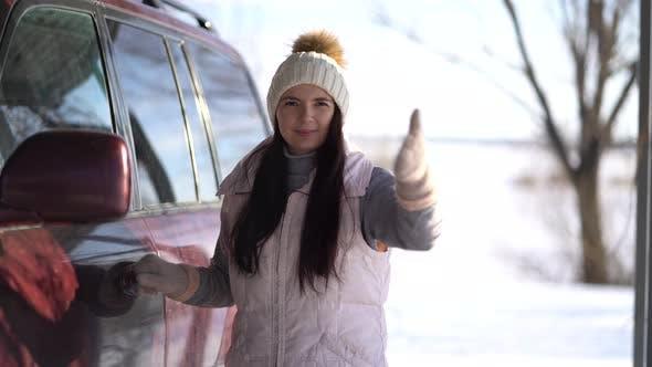 Thumbnail for Junge Frau steht in der Nähe eines Autos und winkte seine Hand an die Kamera im Winter