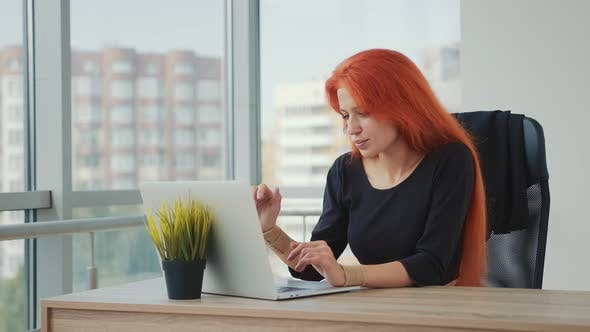 Young Attractive Woman of Caucasian Appearance and Red Hair Working in the Office on a Laptop. The