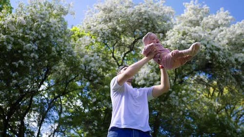 Happy Family, Fatherhood, Parenthood Concept. Happy Father And Baby Playing In Park.