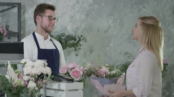 Thumbnail for Service, Young Man Florist Sells Bouquet of Flowers To Happy Woman, Female Buyer Pays for Purchase