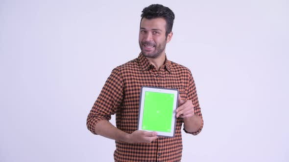 Thumbnail for Happy Bearded Persian Hipster Man Showing Digital Tablet and Looking Surprised