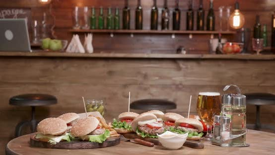 Thumbnail for Very Big Selection of Burgers on Wooden Table in Front of a Bar