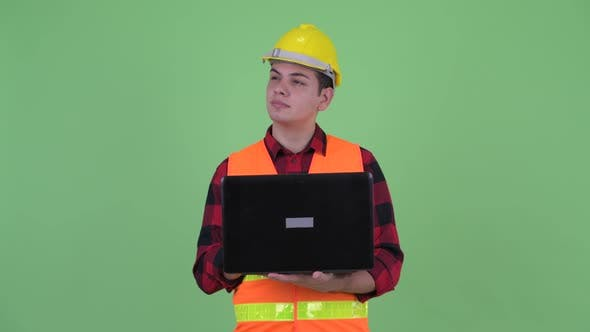 Cover Image for Happy Young Multi Ethnic Man Construction Worker Thinking While Using Laptop