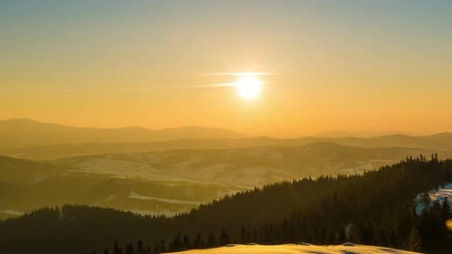 Lapse du coucher du soleil dans la montagne d'hiver