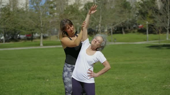 Thumbnail for Smiling Senior Woman Training with Coach on Green Lawn