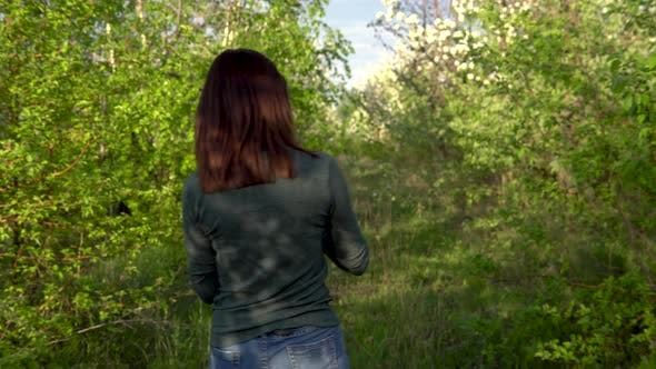 Thumbnail for A Young Woman Walks Between Apple Trees. A Girl Walks Through a Flowering Garden. Back View.