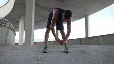 Athlete in Sportswear Warms Up on a City Parking Garage