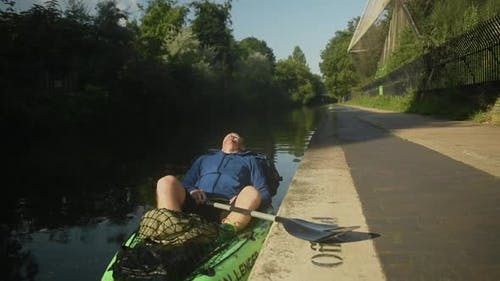 An adult man rests on the side of a river in his green kayak taking a moment to breathe in thoughtfu