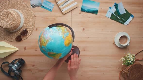 Female Hands Rotating Globe