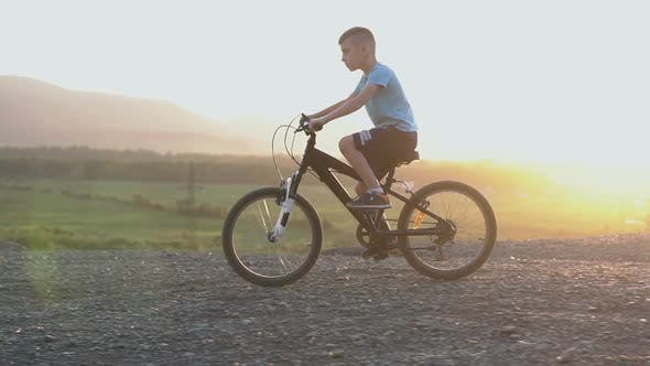 Cover Image for Boy in Blue T-shirt Who Rides a Black Bike in a Mountainous Place at the Summer