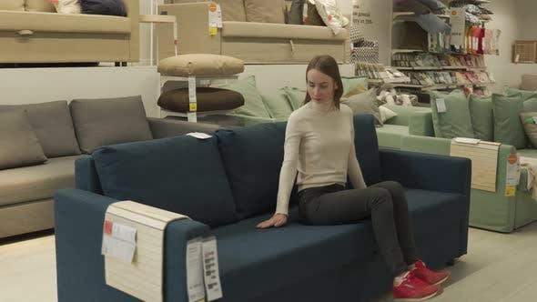 Female Customer Choosing Sofa in Shopping Center
