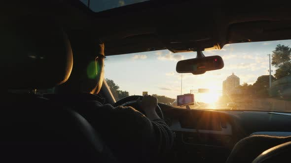 Thumbnail for Young Driver Driving a Car. Sunset Rear View