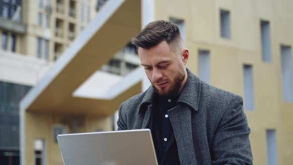 Portrait of a positive man with a laptop. Handsome bearded businessman working on a laptop